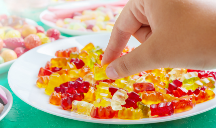 Hand takes a sweet from a plate of colourful gummy bears.